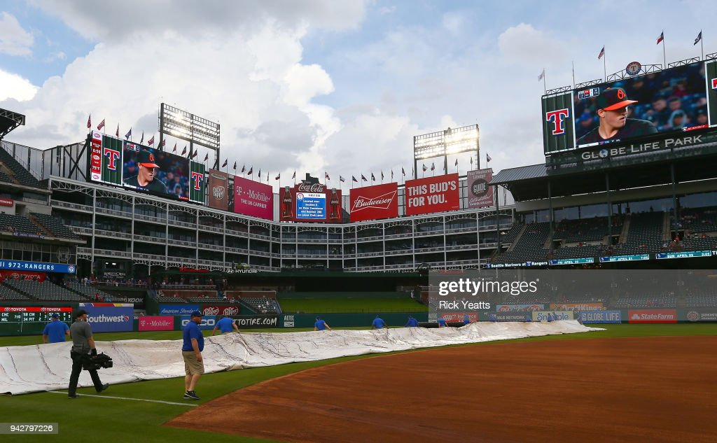 The Texas Rangers ground crew removes the tarp off the infield during a forty five minute rain delay before the game against the Toronto Blue Jays at Globe Life Park in Arlington on April 6, 2018 in Arlington, Texas.