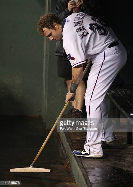 The Texas Rangers' Josh Hamilton squeegees the dugout after a nearly twohour rain delay against the Los Angeles Angels at the Rangers Ballpark in...