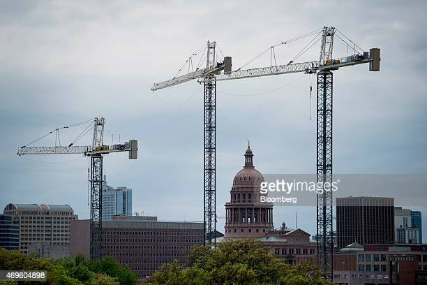 The Texas State Capitol building stands past construction cranes at the University of Texas at Austin campus in Austin Texas US on Saturday April 4...