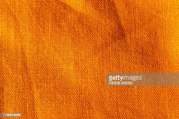 the texture of crumpled cotton linen carrot orange red color fabric texture background - textile stock pictures, royalty-free photos & images