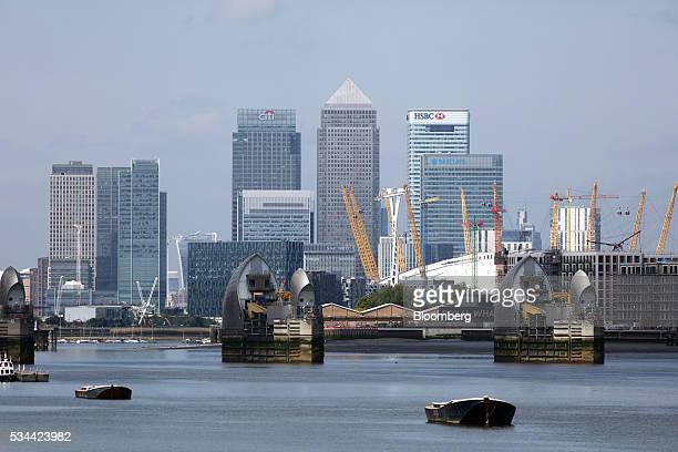 The Thames barrier stands on the River Thames against a backdrop of Canary Wharf business financial and shopping district in London UK on Thursday...