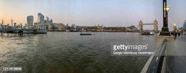the thames river and its boardwalk with tower bridge in the background - london, england - panoramic stock pictures, royalty-free photos & images