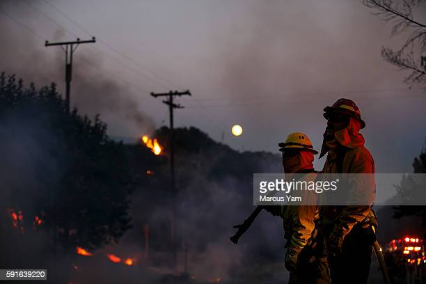 The the full moon in the background firefighters monitor the Blue Cut fire traveling on the side of Lytle Creek Road in San Bernardino County Calif...