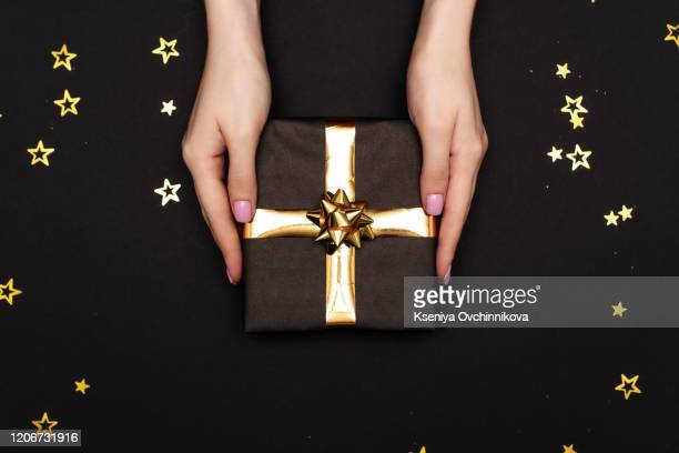 the theme of celebrations and gifts: a man in a black suit holding a exclusive gift packaged in a black box with gold ribbon, beautiful and expensive gift on a dark red background in studio isolated - jewellery stock pictures, royalty-free photos & images