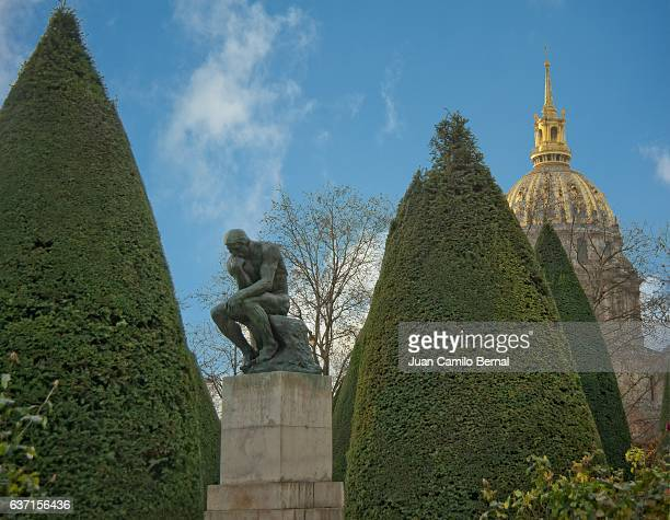 The Thinker (Le Penseur) at the Rodin Museum in Paris, France, with the dome of Les Invalides in the back