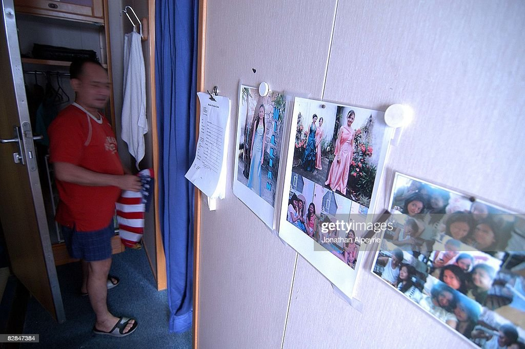 The third chief engineer is grabbing an American flag from his closet during a rest time, on July 20, 2008, in France. Photos of his family are attache to the wall, each men are usually gone for three months at a time.