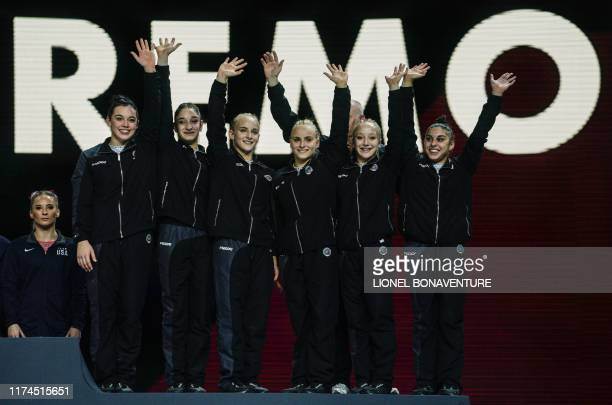 The third placed team of Italy celebrate on the podium after the women's team final at the FIG Artistic Gymnastics World Championships at the...