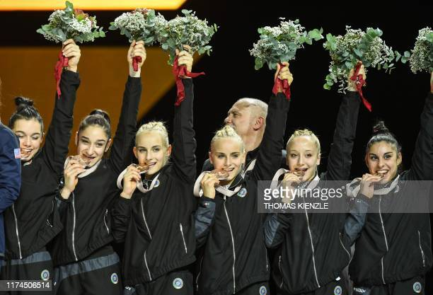 The third placed team of Italy celebrate with their bronze medals on the podium after the women's team final at the FIG Artistic Gymnastics World...