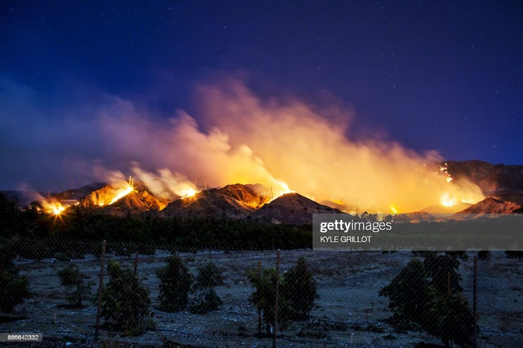 TOPSHOT - The Thomas Fire burns along a hillside near Santa Paula, California, on December 5, 2017. More than a thousand firefighters were struggling to contain a wind-whipped brush fire in southern California on December 5 that has left at least one person dead, sent thousands fleeing, and was choking the area with thick black smoke. / AFP PHOTO / Kyle Grillot
