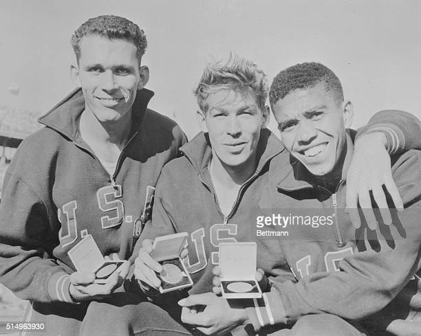The three American Athletes who made a three place sweep in the 400 meter hurdles of the Olympics display smiles and medals here. Left to right:...