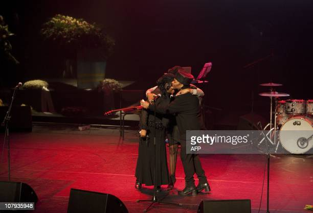 The three Boney M singers embrace during the memorial service for Bobby Farrell in the theatre hall in Amsterdam on January 8 2010 AFP PHOTOANP KIPPA...