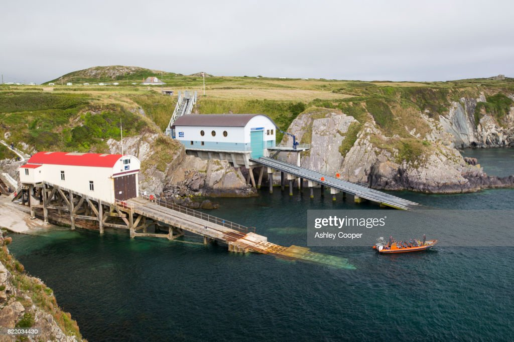 The three generations of St Justinian lifeboat stations, Pembrokeshire, Wales, UK, with a tourist boat trip. : Stock Photo