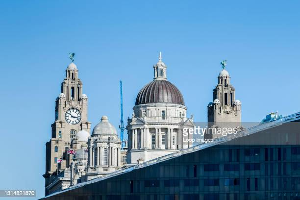 The Three Graces on the world famous Liverpool waterfront seen peaking above a modern building.