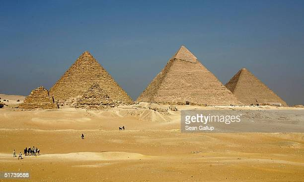 The three large pyramids of Menkaure Khafre and Khufu loom over the horizon November 13 2004 at Giza just outside Cairo Egypt The three large...