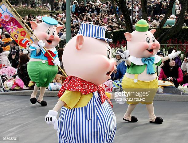 The Three Little Pigs march through the crowd greeting guests during a New Year's Day parade ahead of the 'Year of the Pig' at Tokyo Disneyland in...