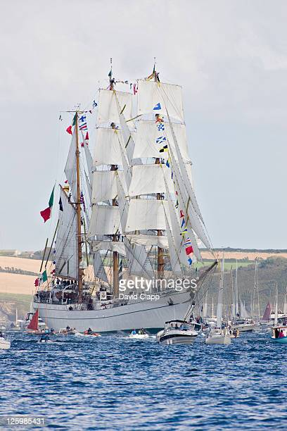 the three masted barque tall ship cuauht?moc at sea surrounded by a flotilla of local yachts and boats. the last of a series of four windjammers built by the naval shipyards of bilbao. falmouth, cornwall, england - cornish flag stock pictures, royalty-free photos & images