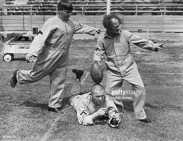 The Three Stooges clowning with a football on a football field in a still from director Albert Rogell's film 'Start Cheering' LR Moe Howard his...