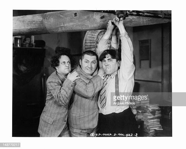 The Three Stooges Larry Fine Curly Howard and Moe Howard standing below pipe in a scene from unidentified film Circa 1940s
