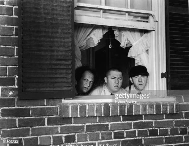 The Three Stooges peer out of a window in a still from an unidentified film LR American actors Larry Fine Curly Howard and Moe Howard