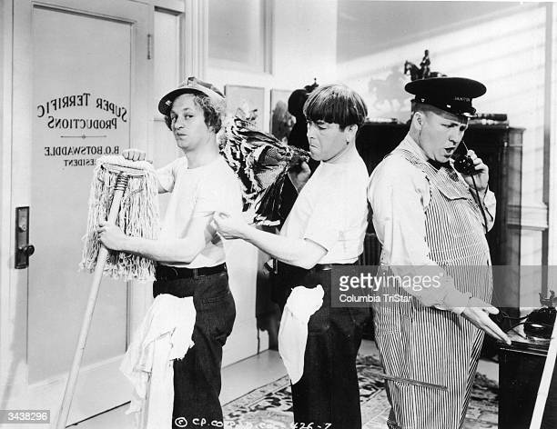 The Three Stooges pose as cleaning men in a still from the film 'Three Missing Links' directed by Jules White Left to right Larry Fine Moe Howard...