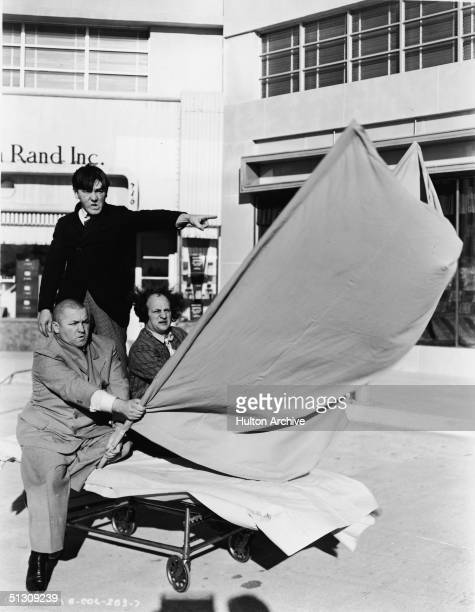 The Three Stooges ride a hospital gurney like a makeshift sailboat in a still from an unidentified film LR American actors Curly Howard Moe Howard...