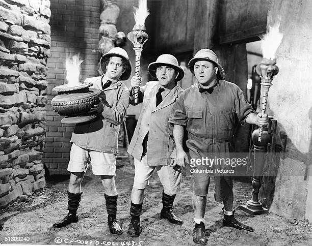 The Three Stooges wearing safari outfits hold torches as they explore a cave in a still from an unidentified film LR American actors Larry Fine Moe...