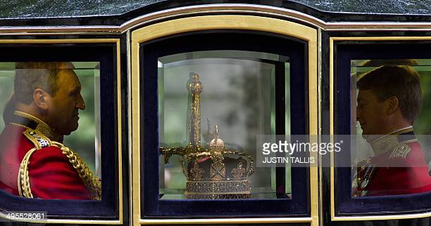 The three symbols of sovereign power the Imperial State Crown the Sword of State and the Cap travel in Queen Alexandra's state coach back along the...