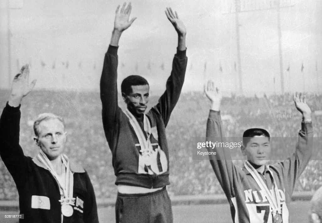 The three winners of the marathon event at the Tokyo Olympics stand side by side on the rostrum, 23rd October 1964. From left to right, they are Basil Heatley of Great British (silver), Abebe Bikila of Ethiopia (gold) and Kokichi Tsuburaya of Japan (bronze). Bikila also set a world record of 2 hours, 12.11 minutes.