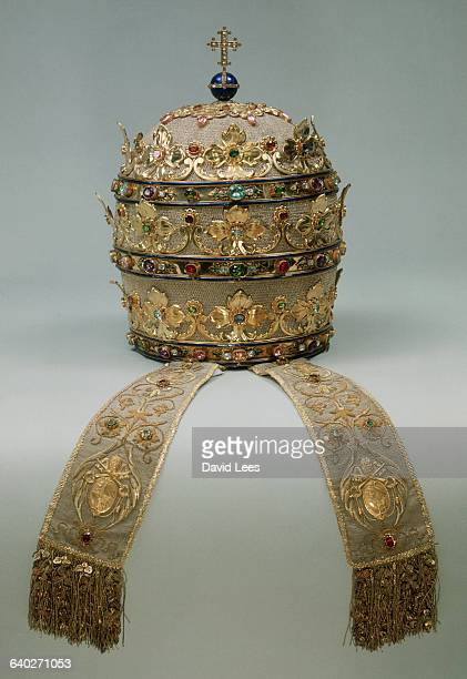 The tiara is fashioned from silver fabric with pale gold leaf blue enamel and semiprecious stones decorate it On the top of the tiara is a cross and...