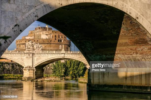 la riva del tevere vicino a castel sant'angelo a roma - ponte ad arco foto e immagini stock