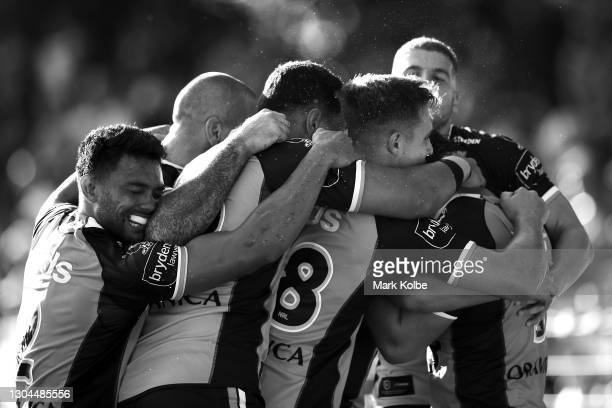 The Tigers celebrate with James Roberts of the Tigers after he scored a try during the NRL Trial Match between the Wests Tigers and the Manly Sea...