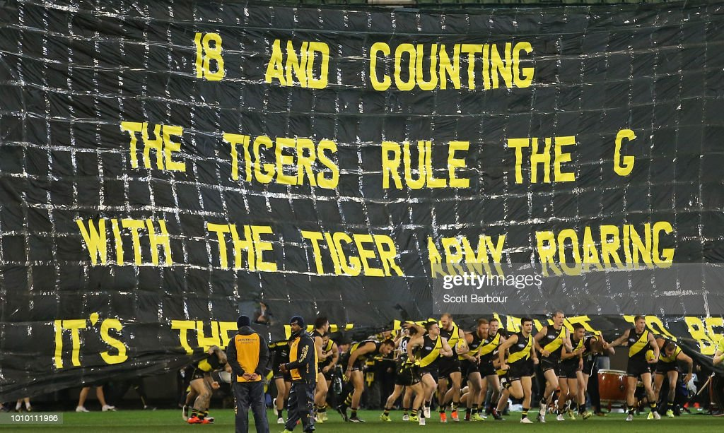 The Tigers run through their banner during the round 20 AFL match between the Richmond Tigers and the Geelong Cats at Melbourne Cricket Ground on August 3, 2018 in Melbourne, Australia.