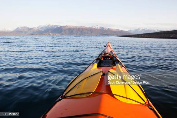 the tip of a canoe pointing towards the kenai mountains, kachemak bay state park - kachemak bay stock pictures, royalty-free photos & images