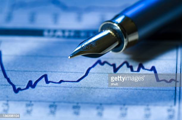 The tip of a fountain pen and a financial graph