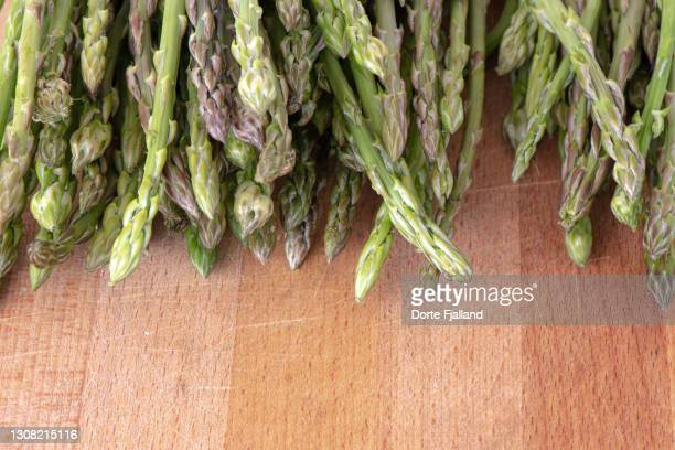 the tips of fresh esparagus on a wooden board - dorte fjalland fotografías e imágenes de stock