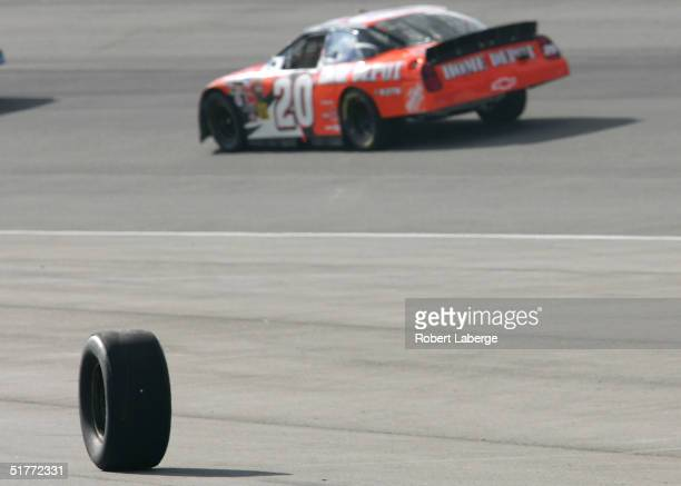The tire of Kurt Busch, driver of the Roush Racing Sharpie Ford, rolls out of pit lane after a pit stop as Tony Stewart driver of the Joe Gibbs...