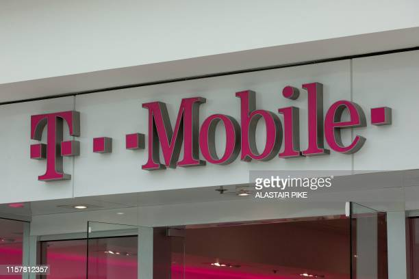 The T-Mobile logo is seen outside a shop in Washington, DC, on July 26, 2019. - US antitrust authorities approved the USD 26 billion merger of...