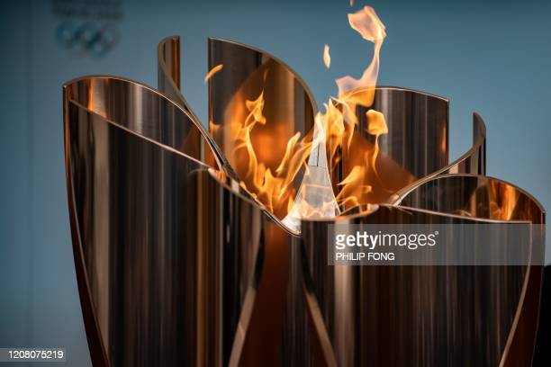 The Tokyo 2020 Olympic flame is displayed outside Fukushima railway station in Fukushima Prefecture on March 24, 2020. - The Olympic torch relay, due...