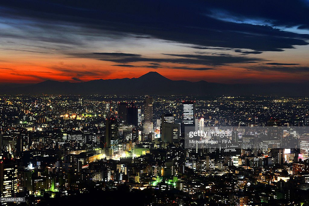 The Tokyo skyline seen at night as the sun sets over Mount Fuji on December 14, 2012 in Tokyo, Japan.