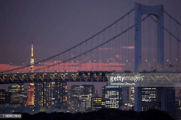 The Tokyo Tower stands illuminated behind the Rainbow Bridge seen from the Odaiba Marine Park which will host Triathlon and Aquatics during the 2020...