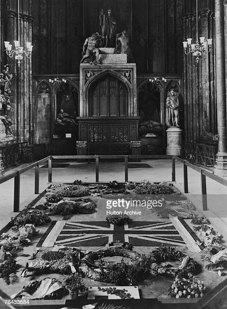 The Tomb of the Unknown Warrior at Westminster Abbey, covered with floral tributes, a British flag and a temporary headstone, 1920.