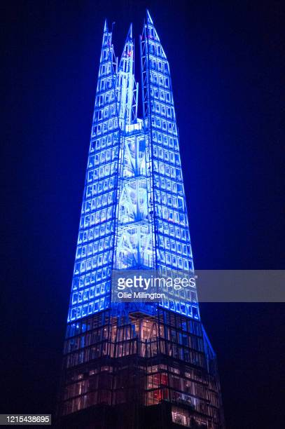 The top 15 levels of The Shard skyscraper, known as The Spire, shining blue in support and thanks to the NHS during the Covid-19 crisis seen on March...