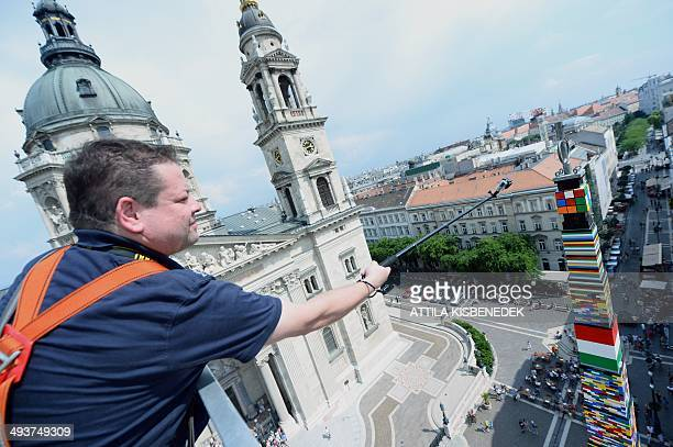 The top of a 3476 meter high tower of Lego plastic bricks with a cube of Hungarian inventor Erno Rubik is seen in front of the St Stephen's Basilica...