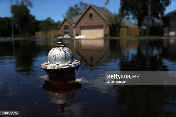The top of a fire hydrant sticks out of floodwaters in front of a home on September 7, 2017 in Richwood, Texas. Over a week after Hurricane Harvey...