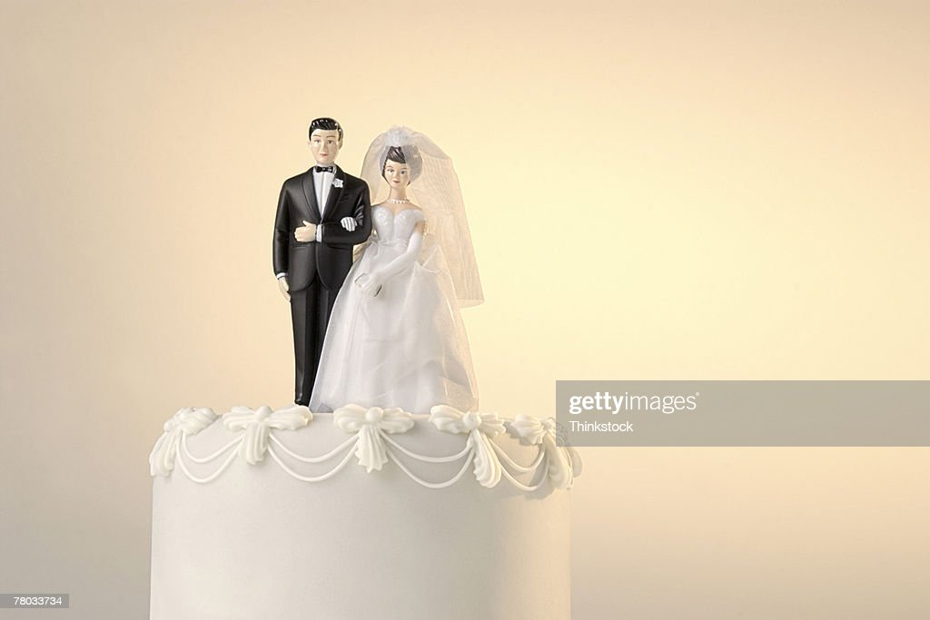 The Top Of A Wedding Cake With A Miniature Bride And Groom Cake ...