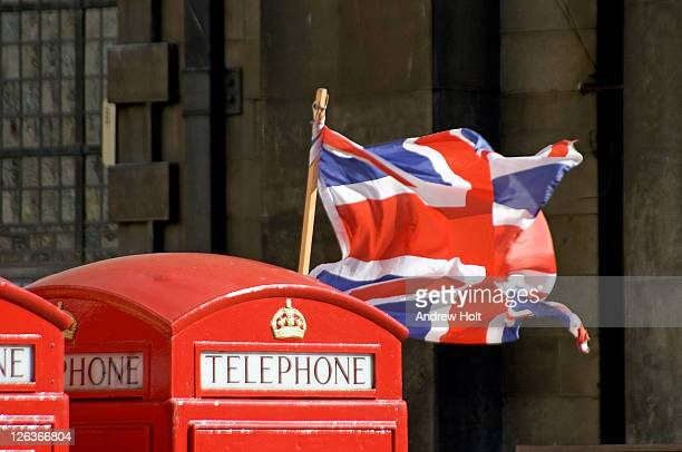 the top of an iconic k2 red telephone box with a union jack flag blowing in wind behind it. - andrew jack stock pictures, royalty-free photos & images
