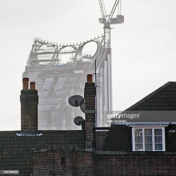 CONTENT] The top of an under construction apartment tower in South London seen from behind a social housing block