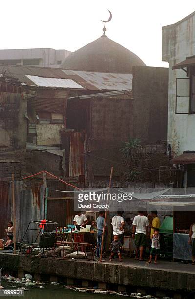 The top of the Golden Mosque pokes into the sky February 7 2002 behind the homes of residents of Quiapo metro Manila Philippines Built by...
