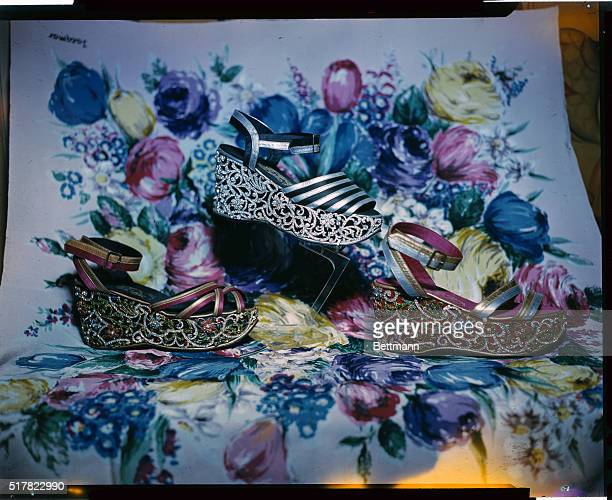 The top one is in black and silver a sandal with normal ankle strap On the wedge is very fine Florentine work with a flower motif in artificial...