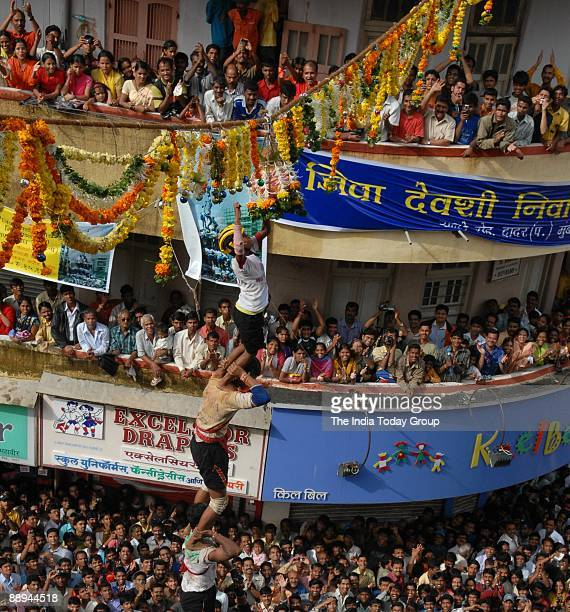 The top person of a human pyramid tries to break the 'Dahi Handi' on the occasion of Krishna Janmashtami the birth anniversary of Lord Krishna in the...